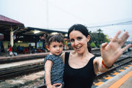 Thailand, Ayutthaya, portrait of mother and little daughter saying goodbye at a train station - GEMF02027