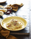 Set table with bowl of spaghetti with pork cheek and seasoning - CUF13856