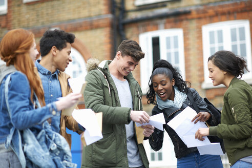 Happy young adult college students reading exam results on campus - CUF13994