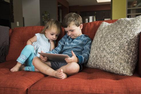 Siblings using digital tablet on sofa - CUF14162