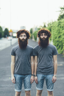 Portrait of identical adult male twins with red hair and beards on sidewalk - CUF14213