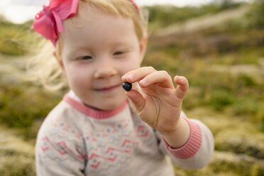 Portrait of young girl outdoors, holding blueberry - CUF14225