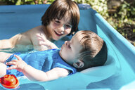 Happy brothers playing in inflatable pool on summer day - CUF14241