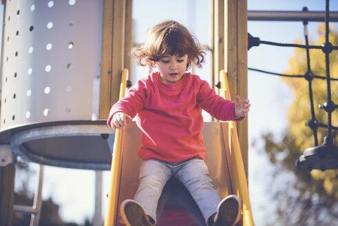 Portrait of little girl sitting on slide at playground - JSMF00203