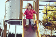 Portrait of little girl sitting on slide at playground - JSMF00206