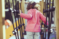 Back view of little girl on climbing frame at playground - JSMF00209