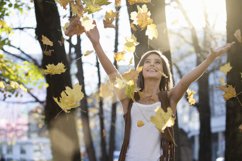 Mid adult woman throwing autumn leaves in sunlit park - CUF14327