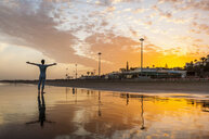 Silhouetted man with arms open on golden sunset beach, Maspalomas, Gran Canaria, Canary Islands, Spain - CUF14357