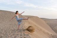 Woman kicking up sand on dune, Maspalomas, Gran Canaria, Canary Islands, Spain - CUF14363