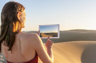 Rear view of woman photographing sunlit dune with digital tablet, Maspalomas, Gran Canaria, Canary Islands, Spain - CUF14366