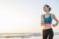 Low angle view of mid adult woman wearing crop top jogging by ocean looking away smiling - CUF14408