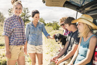 Teenage girl, adult friends and dog sitting on car boot, Bridger, Montana, USA - CUF14516