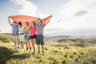 Teenage girl and adult friends holding up blanket, Bridger, Montana, USA - CUF14534