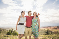 Young man with arm around two young women in hills, Bridger, Montana, USA - CUF14543