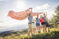 Two young men and female friends holding up blanket on windy hill, Bridger, Montana, USA - CUF14561