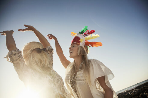 Low angle view of young women wearing feather headdress and sunglasses with hair covering face dancing in sunlight - CUF14573