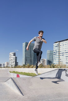 Sportive man jumping in a skatepark in the city - MAUF01401