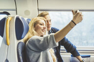 Young couple taking smartphone selfie in train carriage - CUF14611