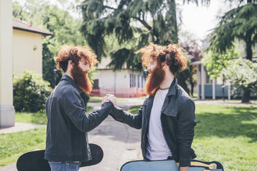 Young male hipster twins with red beards shaking hands in park - CUF14647