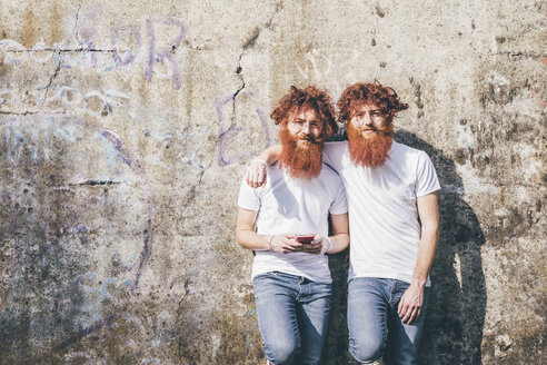 Portrait of young male hipster twins with red beards standing in front of wall - CUF14650