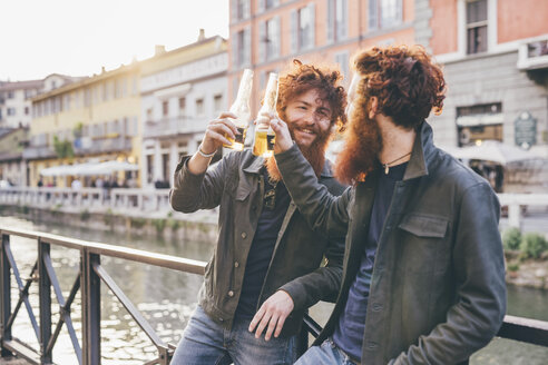 Young male hipster twins with red hair and beards making a toast on canal waterfront - CUF14656