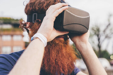 Young male hipster with red hair and beard wearing virtual reality headset - CUF14659
