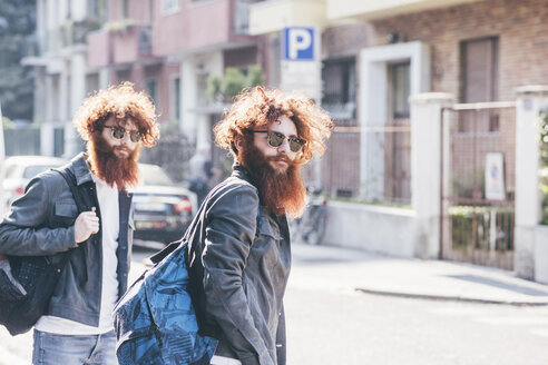 Young male hipster twins with red hair and beards strolling on road - CUF14665