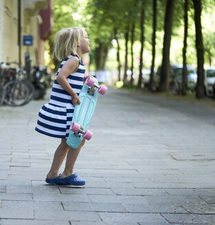 Happy little girl with skateboard on pavement - BEF00106