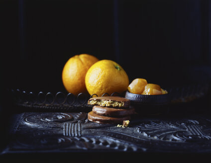 Luxury chocolate coated orange flavoured biscuits and oranges on vintage table, low key - CUF14695