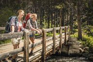 Teenage girl and young female hiker looking out from river footbridge, Red Lodge, Montana, USA - CUF14890