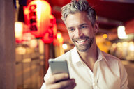 Man looking at smartphone smiling - CUF14938