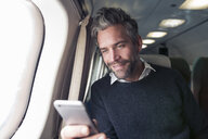 Mid adult man on airplane, using smartphone - CUF14965