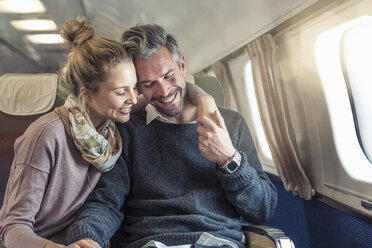 Couple on airplane, hugging, smiling - CUF14968