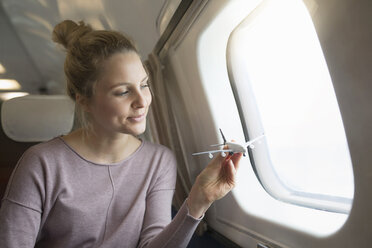 Young woman on airplane, holding model airplane, smiling - CUF14971