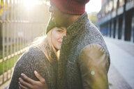 Couple hugging beside steel fence - CUF15007