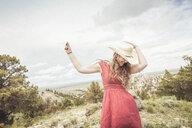 Young woman wearing red dress dancing on hilltop, Cody, Wyoming, USA - CUF15031