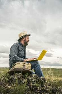 Mature male hiker sitting on rocks using laptop, Cody, Wyoming, USA - CUF15040