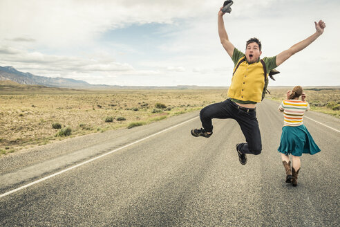 Retro style young man jumping mid air on road, Cody, Wyoming, USA - CUF15043