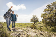 Hiking father and teenage son with map pointing over landscape, Cody, Wyoming, USA - CUF15049