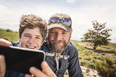 Close up of father and teenage son taking smartphone selfie on hiking trip, Cody, Wyoming, USA - CUF15055