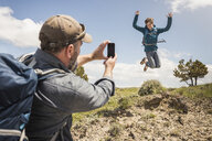 Father photographing teenage son jumping mid air on hiking trip, Cody, Wyoming, USA - CUF15058