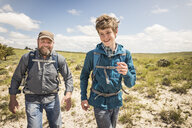 Father and teenage son racing each other on hiking trip, Cody, Wyoming, USA - CUF15064