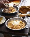 Male hands preparing bowls of pasta e fagioli at table - CUF15076