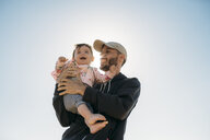 Laughing father holding baby girl at backlight - GEMF02033