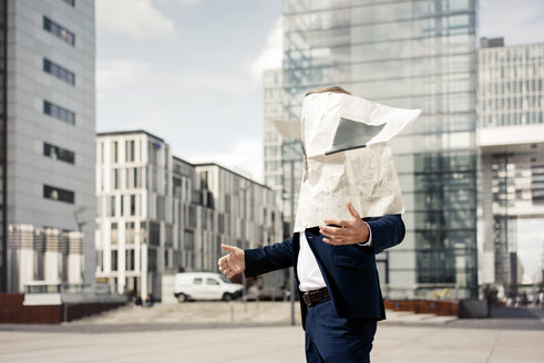 Newspaper covering businessman's face in the city - JOSF02189