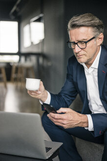 Mature businessman with cup of coffee and laptop using cell phone - JOSF02201