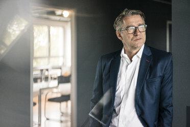 Mature businessman standing in office looking sideways - JOSF02204