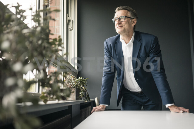 Confident mature businessman looking out of window - JOSF02216