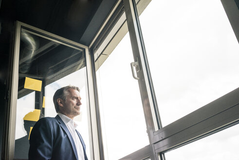 Serious mature businessman looking out of window - JOSF02219