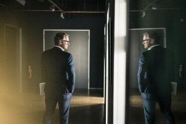 Mature businessman standing on office floor holding laptop - JOSF02228